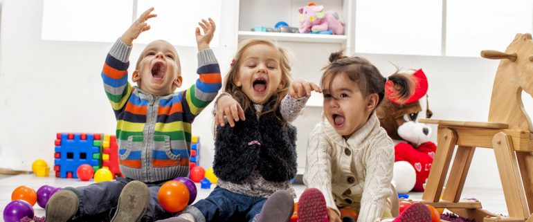 Drei-spielende-lachende-Kinder-im-Zimmer-mit-Spielzeug