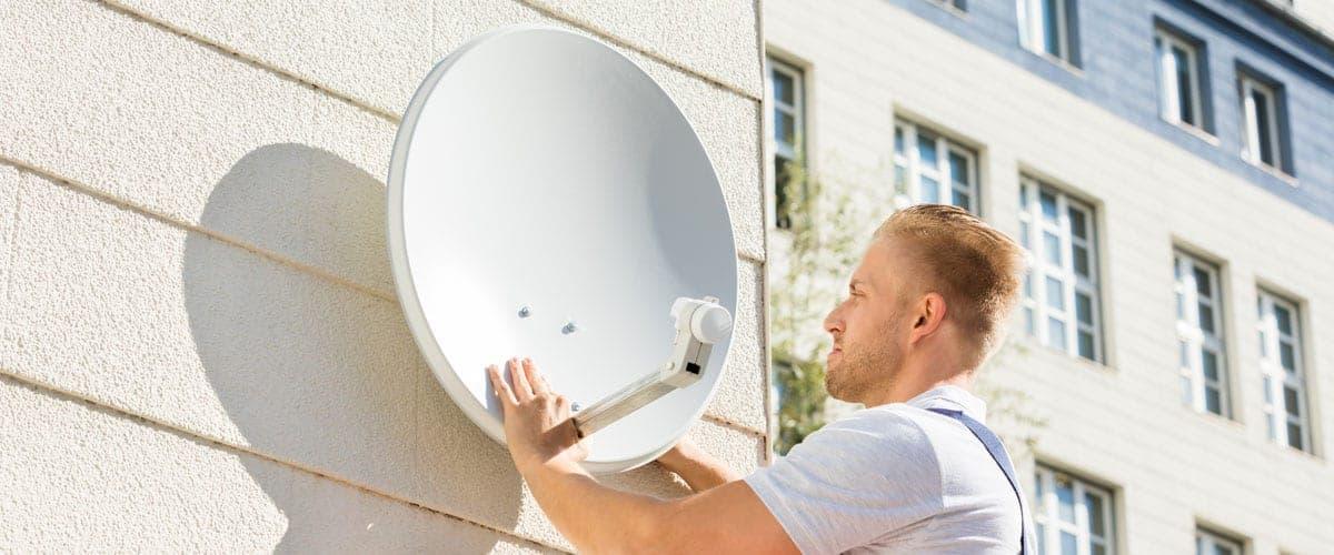 Mann-bringt-Satellitenschuessel-an-Haussfassade-an