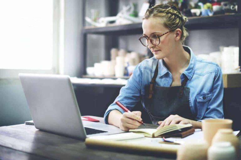 Eine Handwerkerin nutzt ihre Mietwohnung als Büro. Die blonde Frau notiert ihre Aufträge in den Kalender.
