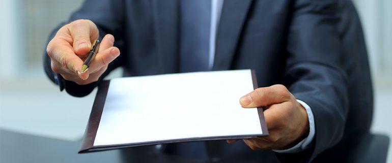 Mann hält Mietvertrag und Stift