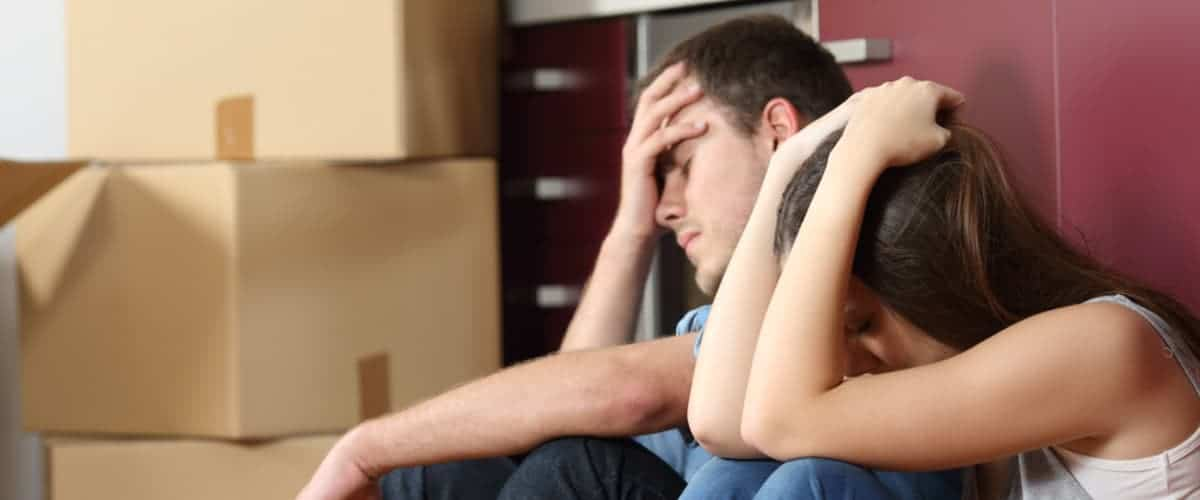 Trauriges Paar sitzt vor Umzugskartons